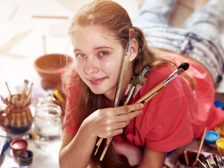 Authentic artist children girl paints with set palette watercolor paints palette and brush in morning sunlight. Sun flare painting in studio on floor. Development of need for creativity in children.