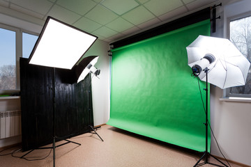 Photostudio with studio equipment: black, green, white background for photography, studio flashes, deflectors, Octoboxes