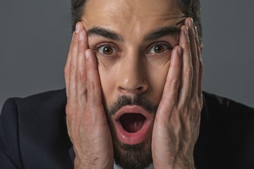 In mute amazement. Close up portrait of shocked bearded man clasping head, staring with astonishment. Isolated on grey background