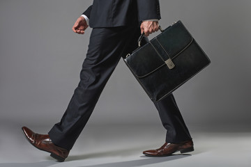 Low angle close up of male legs. Man walking in business suit with suitcase