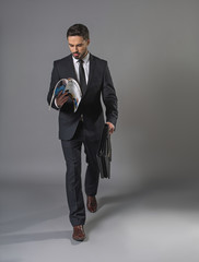 Full length of busy undistracted man in business suit. He is going with briefcase and reading a business periodical