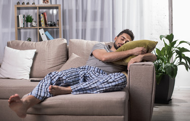 Tranquil young male sleeping on comfortable couch in living room. Bookshelf on background