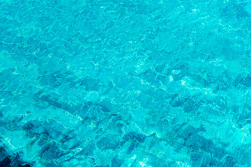 A close up shot of water in swimming pool  as the sunlight reflection. Abstract background.
