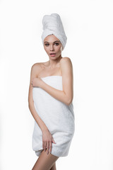 Portrait of shy girl standing wrapped by white bathing towel. She is covering her body by hands and staring forward with bewilderment. Isolated