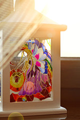 Unique handmade lantern with stained glass painting. Magic candle holder on the window sill behind the curtain