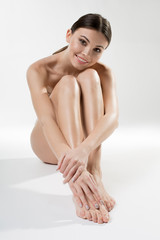 Full length portrait of happy young naked woman sitting on floor elegantly. She is looking at camera and smiling. Beauty concept