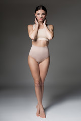 Full length portrait of confident girl standing in beige lingerie. She is expressing temptation