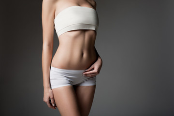 Close up of slender female figure. Young woman is standing in white panties and bandage over breast. Isolated and copy space
