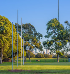 Four Australian football goal posts at a football oval in Carlton, with the city buildings of Melbourne, Australia in the background