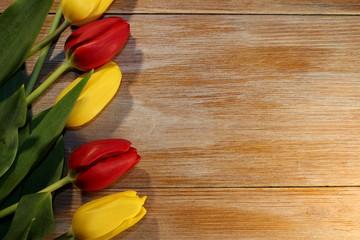 Красивые красные и желтые тюльпаны  которые лежат на деревянных досках