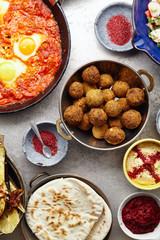 Overhead image of traditional jewish and middle eastern food: falafel, shakshuka, hummus, roasted eggplants and spicy beetroot dip. Israeli cuisine concept
