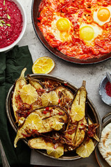 Overhead image of traditional jewish and middle eastern food: shakshuka, roasted eggplants with lemon and spicy beetroot dip. Israeli cuisine concept