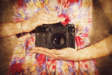 vintage photo of a camera in the hands of a girl, with a texture