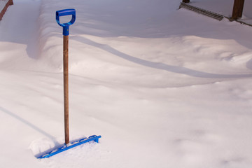 Snow cleaning shovel near the house
