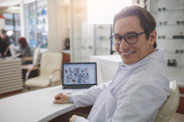 Portrait of cheerful ophthalmologist sitting at desk with laptop while looking at camera. Labor in clinic concept