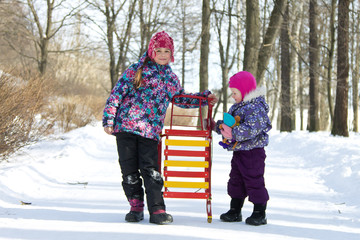 Happy children standing together on a walkway in a snowy winter park an holding the sleds. Kids playing outdoors in winter