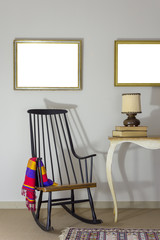 Classic rocking chair and wooden ornate brown desktop photo frame on old style vintage table on background of off white wall with two hanged paintings with clipping path for paintings