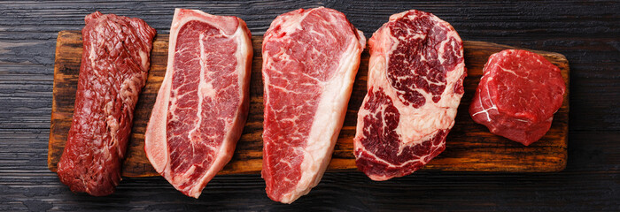 Variety of Raw Black Angus Prime meat steaks Machete, Blade on bone, Striploin, Rib eye, Tenderloin fillet mignon on wooden board