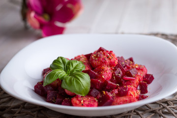Home-made gnocchi and beet root on white plate
