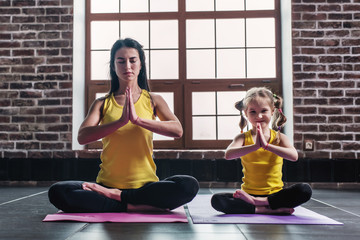Mother and daughter smiling while doing yoga exercises sitting in Padmasana relaxing on mat at home