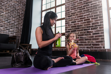 Young Caucasian woman and a happy girl child relaxing after yoga training sitting on mat with legs crossed drinking water, eating banana in sports studio