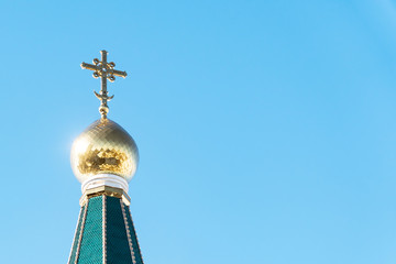 Orthodox cross on the dome of the Church against the clear blue sky