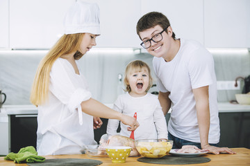 Family together happy young beautiful with a small child preparing dinner in the kitchen at home