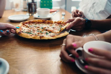 Close-up image of delicious pizza and hands taking slices in Italian restaurant