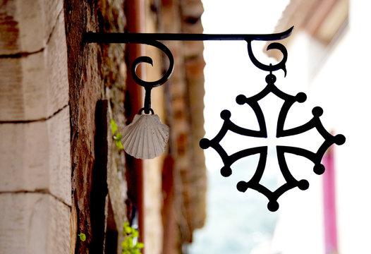 Croix occitane et coquille Saint Jacques. Village de Saint-Guilhem-le-Désert. Près de Montpellier. Sud de la France. Région Occitanie. Chemin de Saint-Jacques-de-Compostelle.