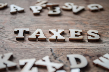 concept wooden letters on wooden table background - Taxes