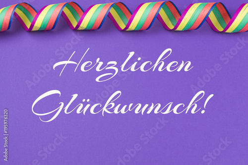 ultra violet background with colorful streamers and the german words for congratulations