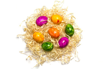 Colored eggs on packing straw. Isolated. Easter 2018. Top view