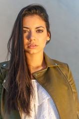 beautiful brown-eyed woman with urban style at sunset in the city