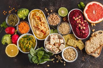 Vegan food background. Vegetarian snacks: hummus, beetroot hummus, green peas dip, vegetables, cereals, tofu. Top view, dark background, copy space.
