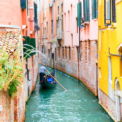 Gondolier on gondola on a canal in Venice, Italy