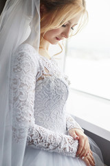 Blonde bride in a white wedding dress and a long veil is waiting for the groom and the beginning of the wedding ceremony. Morning bride-perfect makeup on the woman's face