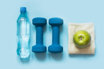 Sport equipmen and fitness equipments on blue background with copy space. Top view.