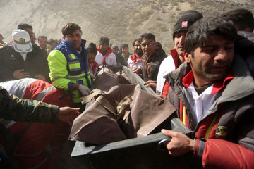Medics and rescuers evacuate the body of a victim killed in a private plane crash