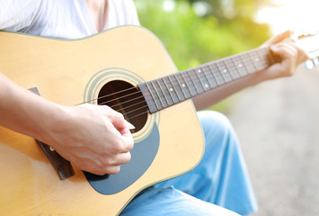 Playing acoustic guitar in the nature at the morning.