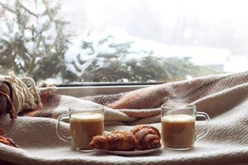 warming the home atmosphere in winter/ two transparent mugs and a croissant on the background of window overlooking snow-covered landscape