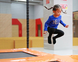 Asian kid girl jumping at trampoline in indoors playground. Active girl having fun at sport center on holiday.
