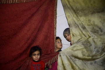 Children stand near curtains in a shelter in the besieged town of Douma