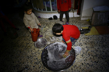 A boy washes dishes in a shelter in the besieged town of Douma
