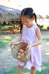 Adorable little asian girl holding a basket with eggs outdoors in the farms.