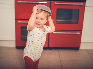 Little boy in the kitchen with collander on his head