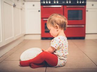 Little boy on kitchen floor with salad spinner