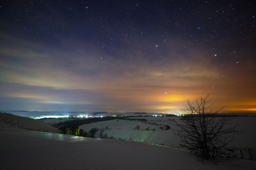 Stars of the night sky are hidden by clouds. Snowy winter landscape at dusk. City in the valley.