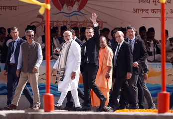 India's Prime Minister Narendra Modi, French President Emmanuel Macron and Chief Minister of India's most populous state of Uttar Pradesh, Yogi Adityanath walk before boarding a boat in Varanasi