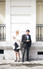 Man and woman with umbrella texting on smartphone