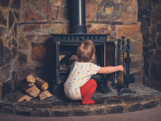 Little boy playing with the log burner